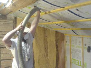 Joel from Ecologis blowing in the cellulose insulation